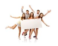 Group of happy students. Group of happy young teenager students standing and smiling with blank placard board isolated on white background Stock Image