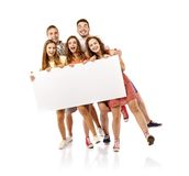Group of happy students. Group of happy young teenager students standing and smiling with blank placard board isolated on white background Stock Photo