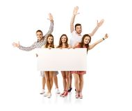 Group of happy students. Group of happy young teenager students standing and smiling with blank placard board isolated on white background Royalty Free Stock Photo