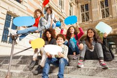 Happy teenage boys and girls with speech bubbles. Group of happy teenage boys and girls, sitting on the stairs outdoors, holding colorful blanked speech bubbles Royalty Free Stock Photography