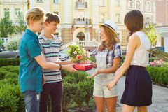 Group of happy teenage friends congratulate their girlfriend on his birthday, give flowers and gift outdoors. royalty free stock images