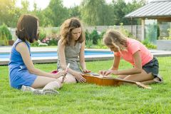 Group of happy teenage girls having fun outdoors with guitar. Come up with new music, sit on green lawn in the yard stock photos