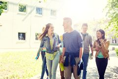 Group of happy teenage students walking outdoors royalty free stock image