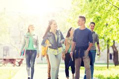 Group of happy teenage students walking outdoors royalty free stock photo