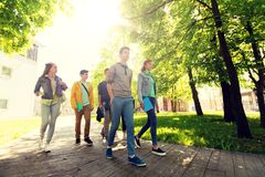 Group of happy teenage students walking outdoors. Education, high school, learning and people concept - group of happy teenage students walking outdoors Royalty Free Stock Image