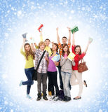 A group of happy teenagers jumping on the grass. A group of smiling teenagers posing together and looking at camera over a blue and snowy background Royalty Free Stock Photo