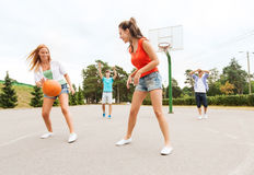 Group of happy teenagers playing basketball Royalty Free Stock Image