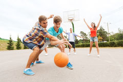 Group of happy teenagers playing basketball Stock Photos