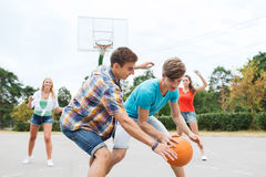 Group of happy teenagers playing basketball Royalty Free Stock Photos