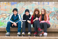 Group of happy teenagers in roller skates sitting. On the street on cloudy autumn day royalty free stock images