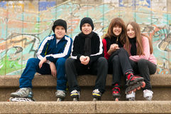 Group of happy teenagers sitting on the street in roller skates. On cloudy autumn day stock images