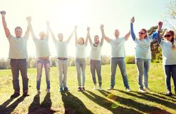 Group of happy volunteers holding hands outdoors stock photos
