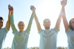 Group of happy volunteers holding hands outdoors Stock Photo
