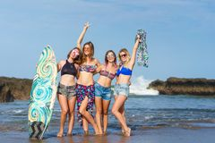 Group of happy women in bikini with surfboard posing in front. Of ocean stock image