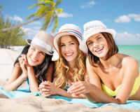 Group of happy women in hats sunbathing on beach. Summer holidays, vacation, travel and people concept - group of smiling young women in hats lying over exotic Royalty Free Stock Photography