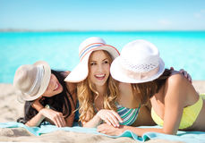 Group of happy women in hats sunbathing on beach. Summer holidays, vacation, travel and people concept - group of smiling young women in hats lying over exotic Stock Images