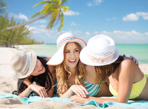 Group of happy women in hats sunbathing on beach. Summer holidays, vacation, travel and people concept - group of smiling young women in hats lying over exotic Royalty Free Stock Photos