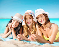 Group of happy women in hats sunbathing on beach Stock Photography