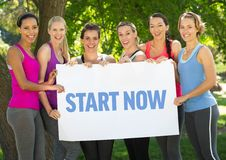 Group of happy women holding placard with text start now. In park royalty free stock photos