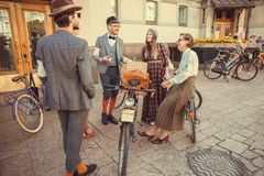 Group of happy women and men in vintage clothing talking about fashion at cosplay festival in Europe Stock Images
