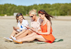 Group of happy women with smartphones on beach Stock Images