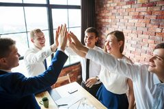 Group of happy young business team celebrating. Group of happy young business team celebrating and high fiving each other stock photos
