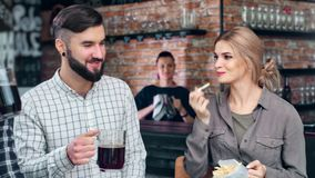 Group of happy young casual friend relaxing at loft pub cozy interior enjoying weekend evening. Medium shot. Smiling girl and guy drinking beer eating french stock footage