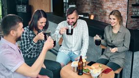 Group of happy young friend drinking beer clinking glasses laughing having positive emotion. At pub. Smiling man and woman relaxing together enjoying stock video