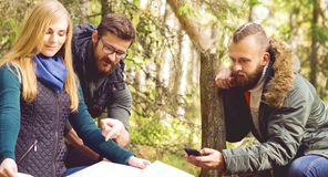 Group of happy, young friends checking a map in forest. Camp, to. Urism, hiking, trip, concept royalty free stock photography