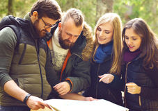 Group of happy, young friends checking a map in forest. Camp, to Royalty Free Stock Photo