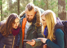 Group of happy, young friends checking a map on a smartphone in. Forest. Camp, tourism, hiking, trip, concept stock photography