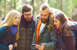Group of happy, young friends checking a map on a smartphone in. Forest. Camp, tourism, hiking, trip, concept stock images