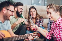 Happy young friends having fun and drinking beer. Group of happy young friends having fun and drinking beer in home interior Royalty Free Stock Image