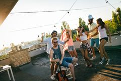 Group of happy friends having party on rooftop royalty free stock photo