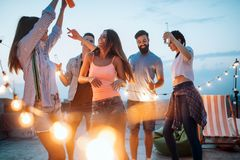 Group of happy young friends having party on rooftop royalty free stock photography