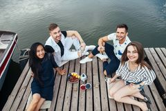 Group of happy young friends relaxing on river wooden pier stock images
