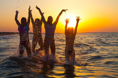 Group of happy young girls jumping at the beach. On beautiful summer sunset Stock Photography