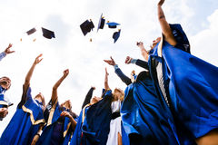 Group of happy young graduates. Image of happy young graduates throwing hats in the air Stock Photos