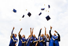 Group of happy young graduates. Image of happy young graduates throwing hats in the air Royalty Free Stock Photography