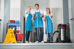 Group Of Happy Young Janitor Showing Thumbs Up. Group Of Happy Young Janitor With Cleaning Equipment Showing Thumbs Up Royalty Free Stock Images