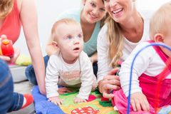 Group of happy young mothers watching their cute and healthy babies. While playing with multicolored toys in a modern daycare center Royalty Free Stock Images