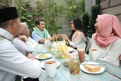 Group happy young muslim greeting in table dining. Group happy young muslim embracing each others in dining table during ramadan celebration Stock Image