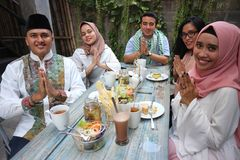 Group happy young muslim greeting in table dining during ramadan. Celebration during ramadan celebration, break fasting Stock Photography