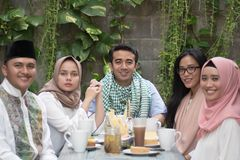 Group of happy young muslim having dinner outdoor looking to cam stock photo