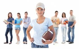 Group of happy young people. Smiling women at front holding football, isolated on white background Stock Photography