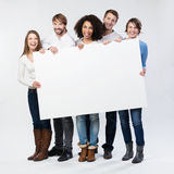 Group of happy young people with a blank sign. Group of diverse multiethnic happy young people posing with a blank white rectabgular sign with copyspace for your Stock Images