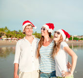 Group of happy young people in christmass hats on Royalty Free Stock Images