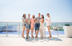 Group of happy young people in colored clothes are drinking champagne at a luxury hotel near the beach. A lot of young stock image