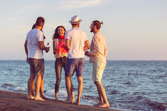 Group of happy young people dancing at the beach on beautiful summer sunset stock photo