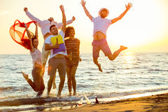 Group of happy young people dancing at the beach on beautiful summer sunset.  Royalty Free Stock Photography